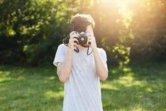 Junger männlicher Fotograf, der Fotos mit seiner Retro- Kamera aufwirft gegen den grünen Hintergrund macht Fotos von den Landscha Stockbild