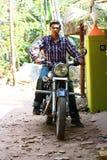 Junger männlicher indischer Stoß, der ein großes schwarzes Fahrrad anstellt Stockbild