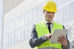 Junger männlicher Ingenieur, der digitale Tablette außerhalb der Industrie verwendet Stockfotografie