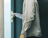 Junger männlicher Jugendlicher im karierten Hemd, das nach Hause verlässt und schließt Tür stockbilder
