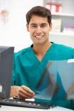 Junger männlicher Krankenhausdoktor am Schreibtisch Stockfotos