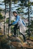 Junger männlicher Läufer mit einer Uhr und Gläsern klettert oben Berg auf Rennstrecke Stockfoto