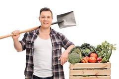 Junger männlicher Landwirt, der eine Schaufel hält Stockfotos