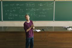 Junger männlicher Lektor im Vorlesungssalsapplaus mit Tafel im Hintergrund stockfoto
