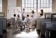 Junger männlicher Manager, der whiteboard in einem Geschäftstreffen verwendet lizenzfreies stockbild
