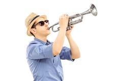 Junger männlicher Musiker, der Trompete spielt Lizenzfreies Stockfoto
