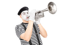 Junger männlicher Pantomimekünstler, der eine Trompete spielt Stockbild