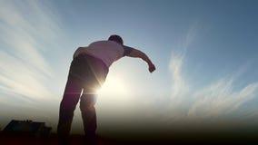 Junger männlicher parkour tricker Pullover führt überraschende leichte Schläge vor der Sonne durch stock footage