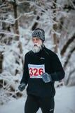 Junger männlicher Rüttler, der durch eine schneebedeckte Parkgasse läuft Gesicht und Bart im Frost Stockfoto