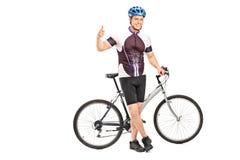 Junger männlicher Radfahrer, der einen Daumen aufgibt Lizenzfreies Stockfoto