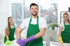Junger männlicher Reiniger bei der Arbeit im Büro stockfotografie
