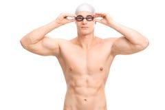 Junger männlicher Schwimmer mit einer Schwimmenkappe und -schutzbrillen Stockfoto