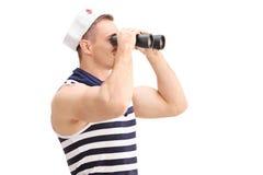 Junger männlicher Seemann, der durch Ferngläser schaut Stockfotografie