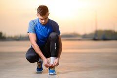 Junger männlicher Sportler, der Laufschuhe bindet und für städtischen Lauf bei Sonnenuntergang sich vorbereitet Gesunder Lebensst stockbild