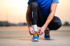 Junger männlicher Sportler, der Laufschuhe bindet und für städtischen Lauf bei Sonnenuntergang sich vorbereitet Gesunder Lebensst lizenzfreie stockfotografie