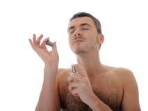 Junger männlicher Sprayduftstoff des Makroschusses auf seiner Haut Stockfotografie