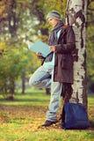 Junger männlicher Student, der auf einem Baum sich lehnt und ein Buch in einer Gleichheit liest Stockbild