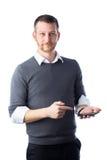 Junger männlicher Student, der auf Smartphone zeigt Lizenzfreie Stockfotos