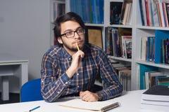 Junger männlicher Student in der Bibliothek Lizenzfreies Stockfoto