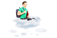 Junger männlicher Student mit der Schultasche, die auf Wolken und dem Schauen sitzt Stockbild