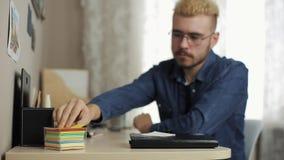 Junger männlicher Student mit stilvollem Haarschnitt mit Gläsern macht Anmerkungen auf Aufkleber auf der Schreibtischtabelle mit  stock video footage