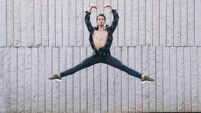 Junger männlicher Tänzer, der Ballettbewegungen durchführt Lizenzfreie Stockfotos