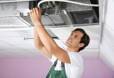 Junger männlicher Techniker, der Klimaanlage repariert stockfoto