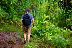 Junger männlicher Tourist, der auf der berühmten Kalalau-Spur entlang Küste Na Pali der Insel von Kauai wandert Lizenzfreies Stockbild