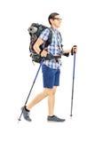 Junger männlicher Tourist, der mit Wanderstöcken geht Lizenzfreie Stockfotografie