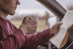 Junger männlicher Tourist, der neues coffe im Auto im breiten Wald in aurumn Jahreszeit b trinkt stockfotos