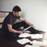 Junger männlicher Unternehmer macht das Brainstorming, das auf dem Boden in der Wohnung sitzt Kreative Annäherung an Geschäft lizenzfreie stockbilder