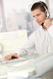 Junger männlicher Verteiler, der im Büro arbeitet stockfoto