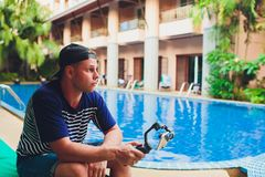 Junger männlicher Videoblogger schafft Videoinhalt für seinen Kanal Videoaufnahmen für Benutzer beim Sitzen durch das Pool Man lizenzfreies stockbild