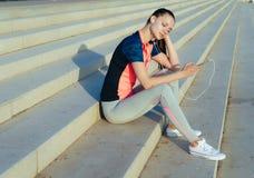 Junger müder Frauenläufer entspannendes afret arbeiten, hörende Musik aus stockfotografie