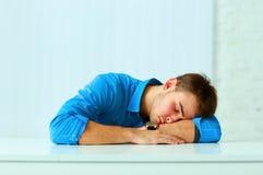 Junger müder Geschäftsmann, der am Arbeitsplatz schläft Stockfotografie