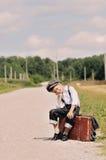 Junger müder Reisender, der auf der Straße sitzt Lizenzfreie Stockfotos