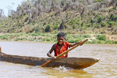 Junger madagassischer afrikanischer Junge, der traditionelles Kanu rudert Lizenzfreie Stockfotos