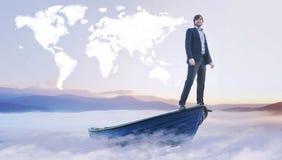 Junger Manager unter der Wolkenweltkarte Stockfotografie