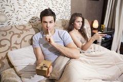 Junger Mann überrascht seine Freundin mit Geschenk Stockbild