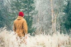 Junger Mann allein gehend im Freien mit nebeliger skandinavischer Waldnatur auf Hintergrund Stockfoto