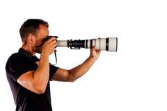 Junger Mann als Detektiv, der mit einem Tele-lense lokalisiert auf weißem Hintergrund fotografiert stockfotografie