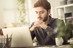 Junger Mann arbeitet an seinem Laptop Lizenzfreie Stockfotos