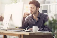 Junger Mann arbeitet an seinem Laptop Stockfotos