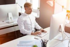 Junger Mann am Arbeitsplatz im Büro Lizenzfreie Stockbilder