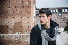 Junger Mann außerhalb des Gebäudes, das nach links schaut Lizenzfreie Stockfotos