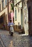 Junger Mann auf Bewegungsrollerreiten durch die Straßen der alten Stadt Rovinj Istria Kroatien Lizenzfreies Stockfoto