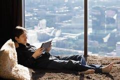 Junger Mann auf Couch mit Tablette stockfotografie