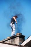 Junger Mann auf dem Dach des Hauses Stockbild