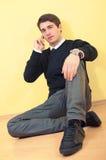 Junger Mann auf dem Fußboden mit Telefon lizenzfreie stockfotos
