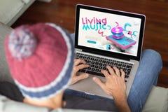 Junger Mann auf dem Sofa mit Musikwebsite lizenzfreie stockfotografie